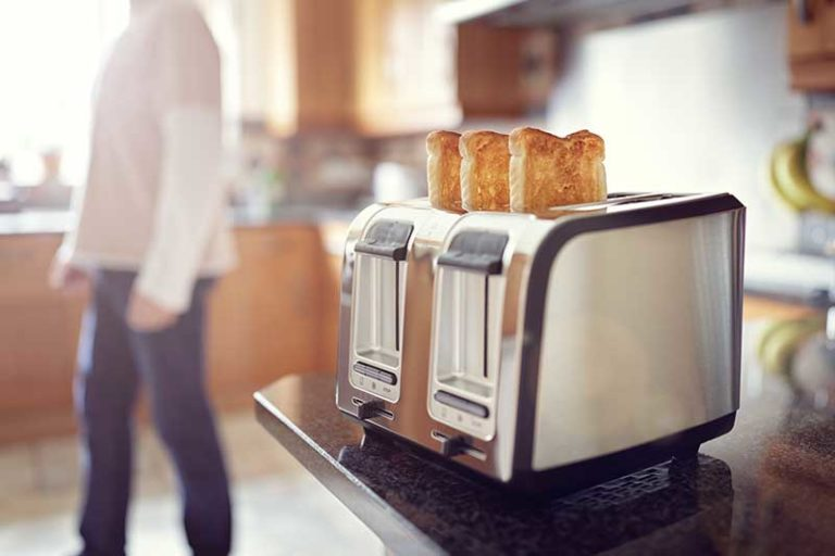 toaster with toasted bread in and woman in background
