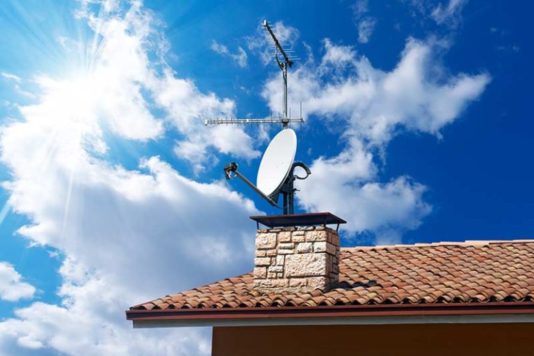 tv-satelite-against-blue-sky-on-roof-of-house